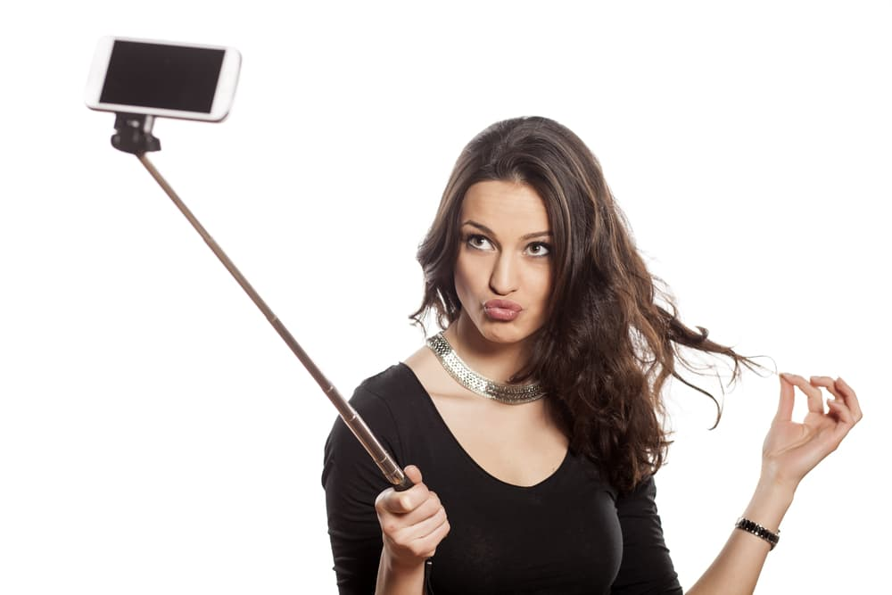 pretty brunette making selfie with a stick
