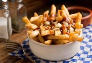 Classic French Canadian poutine with french fries, gravy, and cheese curds on a rustic tabletop.