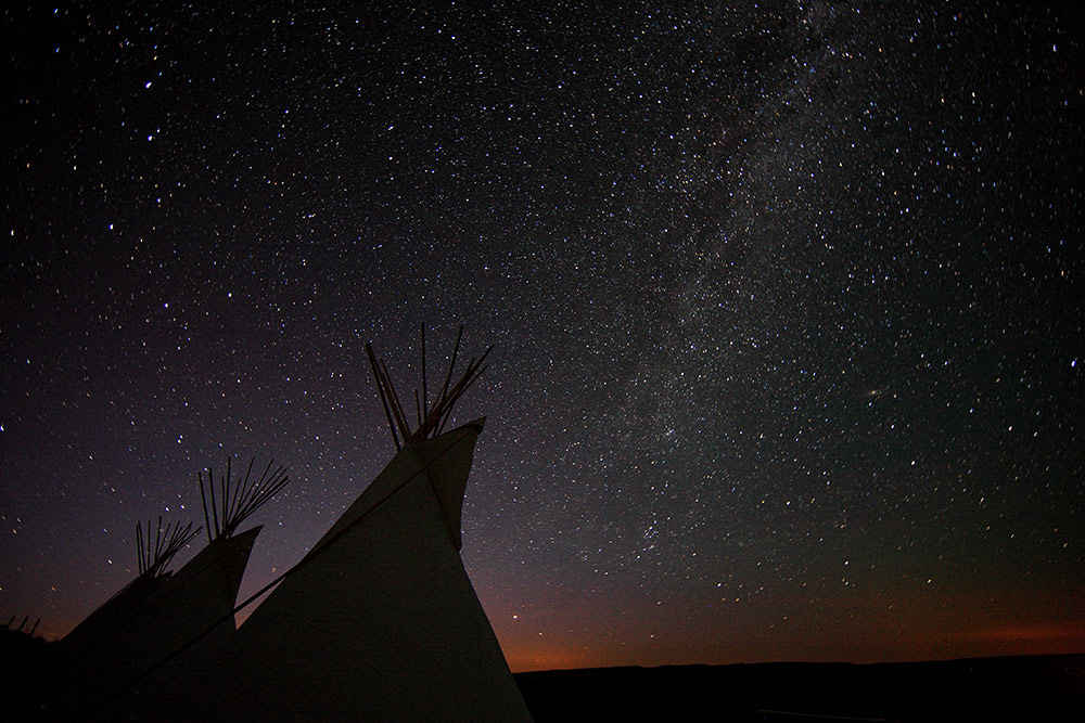 Tipis under a starry sky with a touch of red light at the horizon in Grasslands National Park.