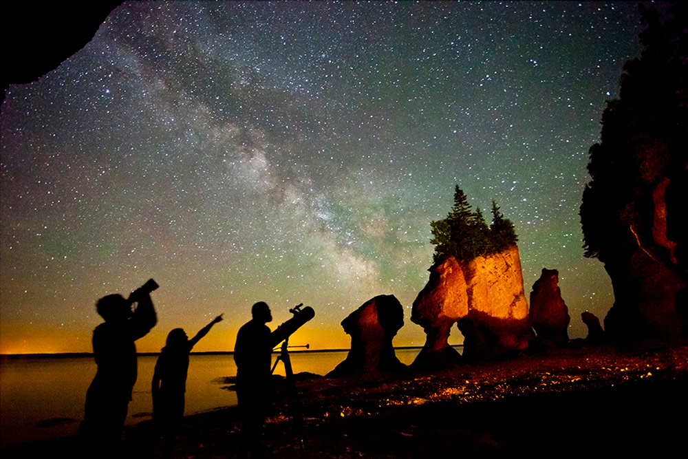 Three people stand near the Hopewell Rocks during low tide after dark. They use telescopes to look toward the sky with lots of stars.