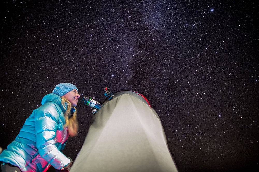 Young woman in winter wear looks through the lens of a large telescope at Jasper Planetarium. A dark sky with thousands of stars is above her.