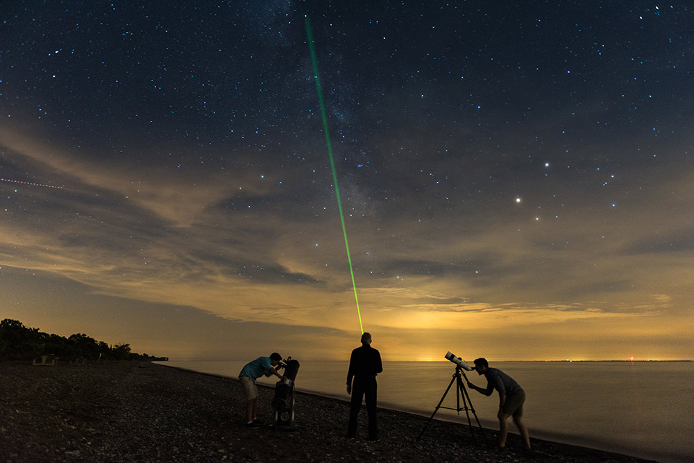 Three researchers looking up at the stars with telescopes from the waterfront at Pelee Point National Park at dusk.
