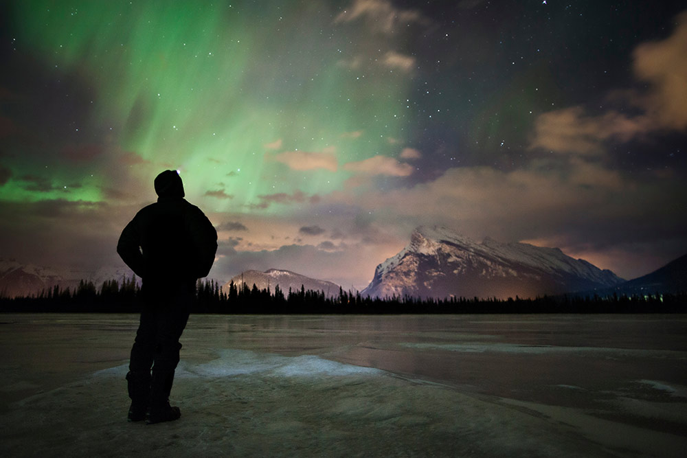 Man in silhouette stands on frozen Vermilion Lake looking up at the Northern Lights and a starry sky with snowy mountains and trees on the horizon.