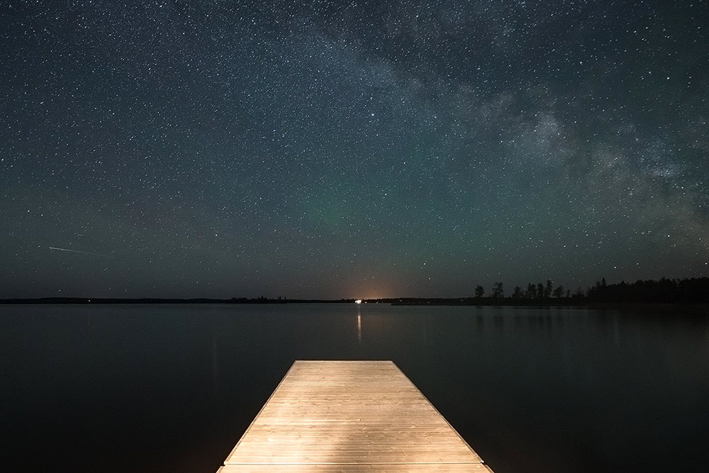 Looking out over the end of a wooden dock at Whiteshell Provincial Park. The water is perfectly smooth and the sky is sprinkled with stars.