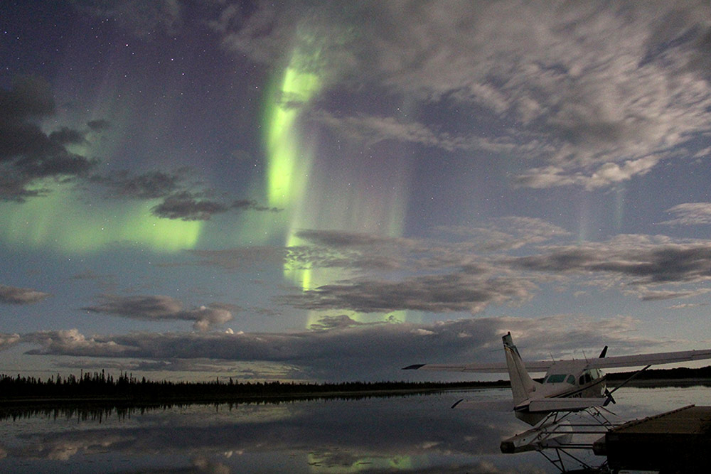 A white seaplane docked on the water at Wood Buffalo National Park under a starry sky and green northern lights.