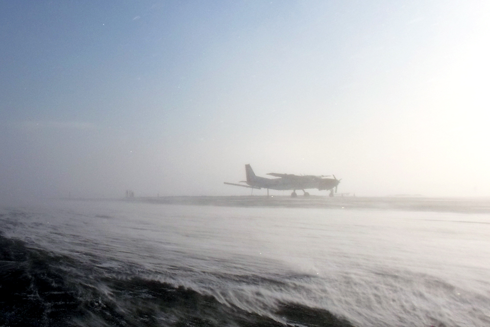 Plane on runway in blizzard in one of the windiest cities in Canada, Baker Lake, NU