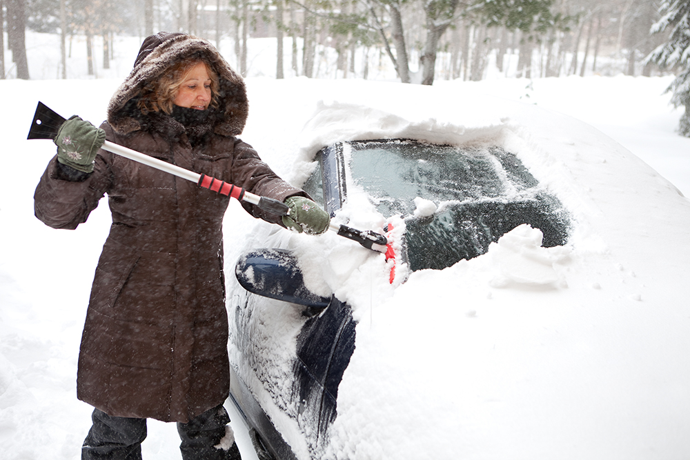 Woman digs car out from snow in Gander, NL, one of the snowiest places in Canada