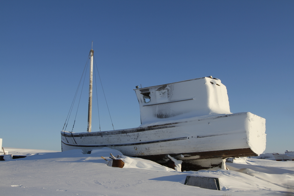 Boat frozen in snow in one of Canada's coldest cities, Rankin Inlet, NU