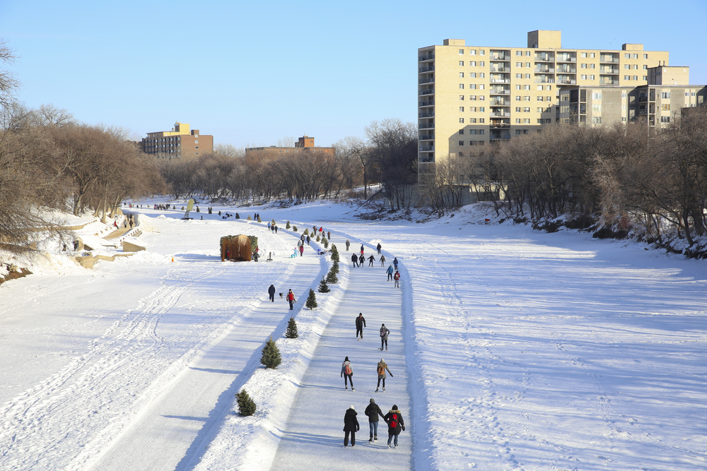 People ice skating on the frozen river in Winnipeg, MB, the coldest city in Canada