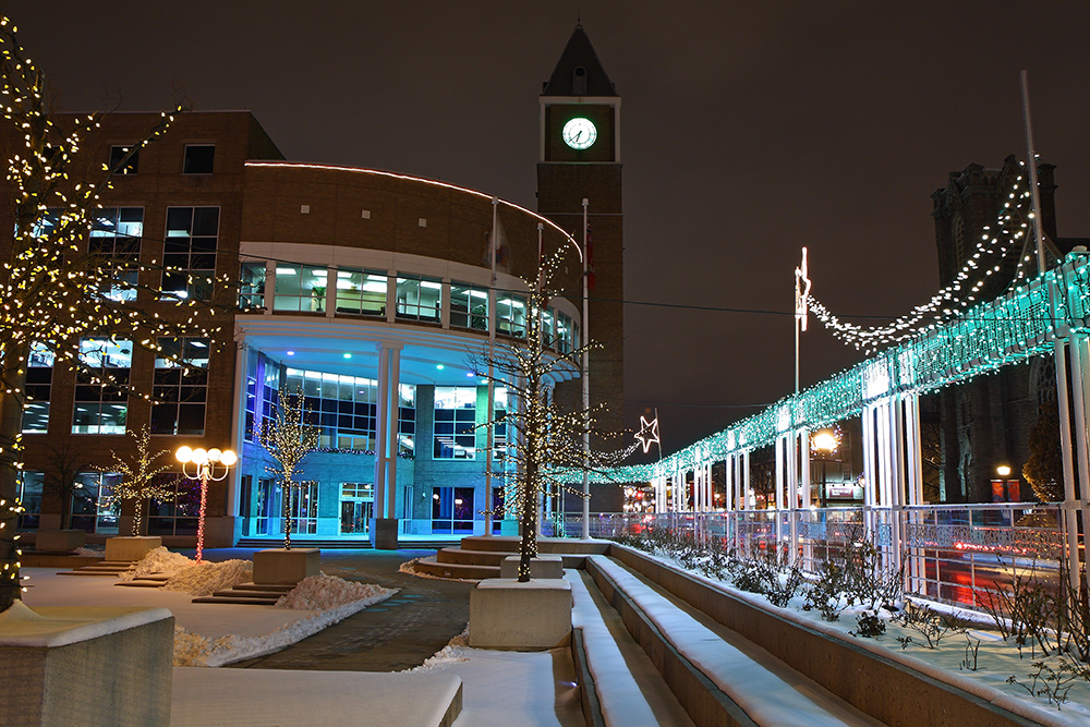 Brampton's city hall at night with holiday lights illuminating the exterior courtyard