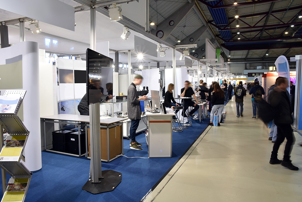 Indoor trade show with various booths and businesses, with people visiting each booth