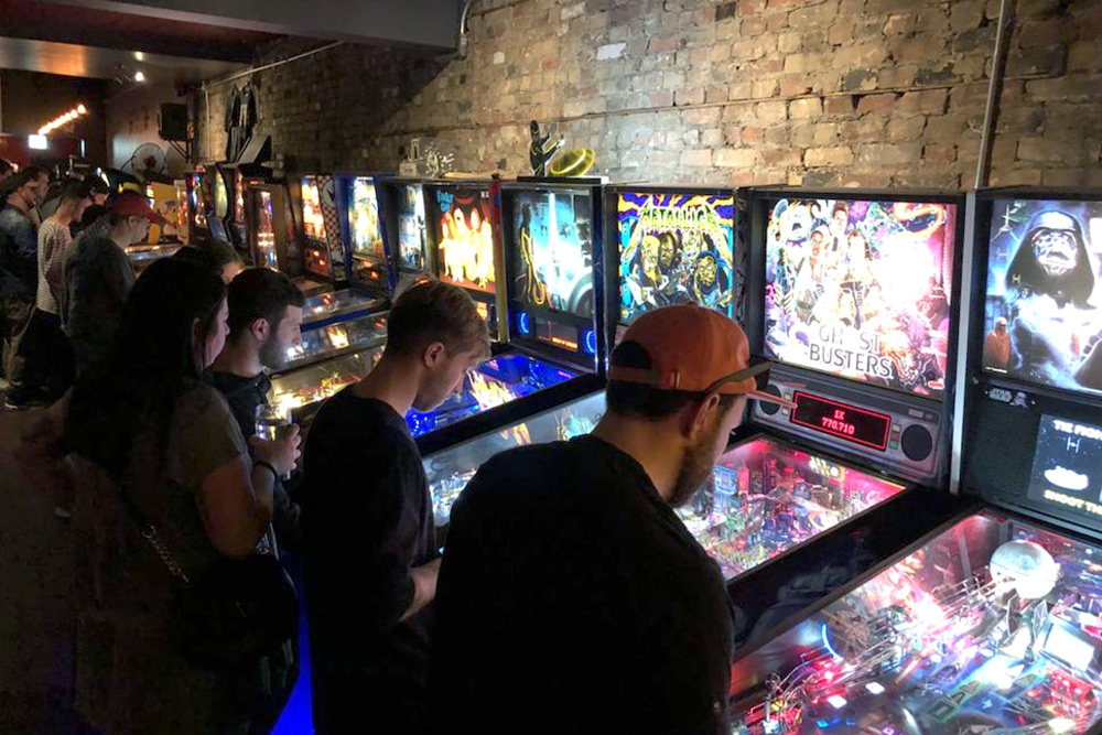 People play old-school games at an arcade bar, one of the top bachelor party ideas in Toronto