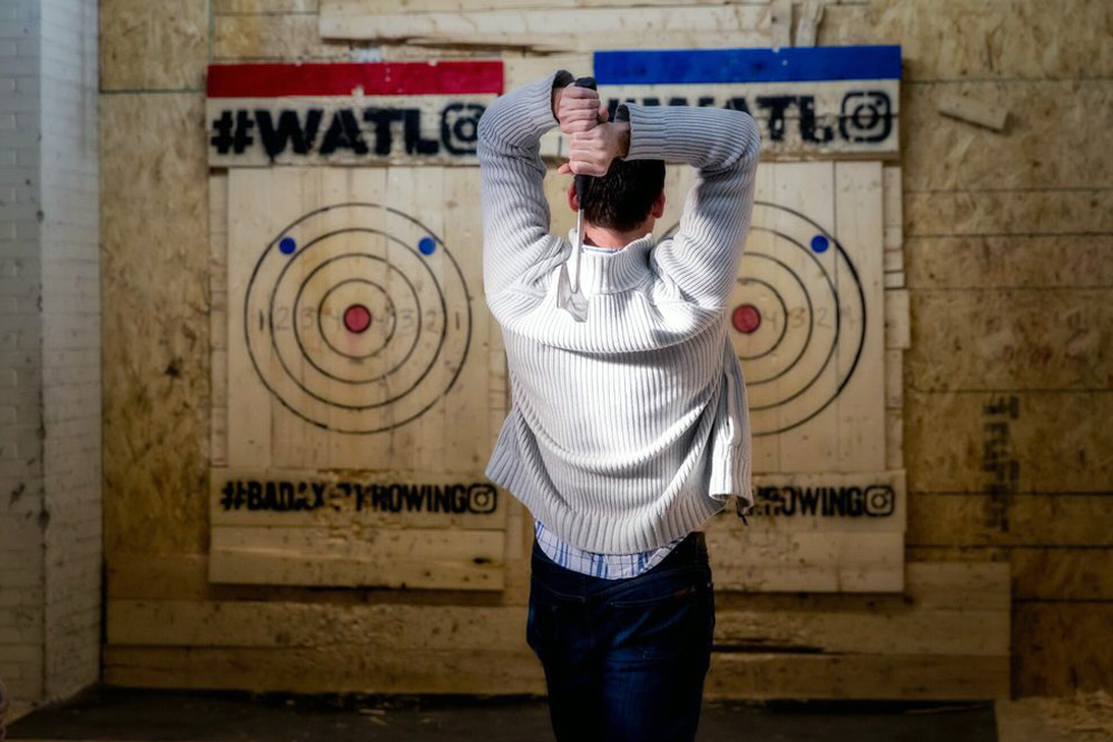 Man aims for the bullseye at axe throwing, a top bachelor party sport in Toronto.