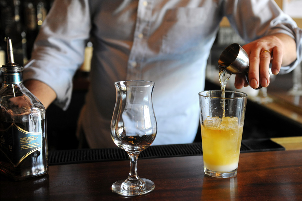 Man pours liquor and mixes together at a bartender class, a top bachelor party activity in Toronto.