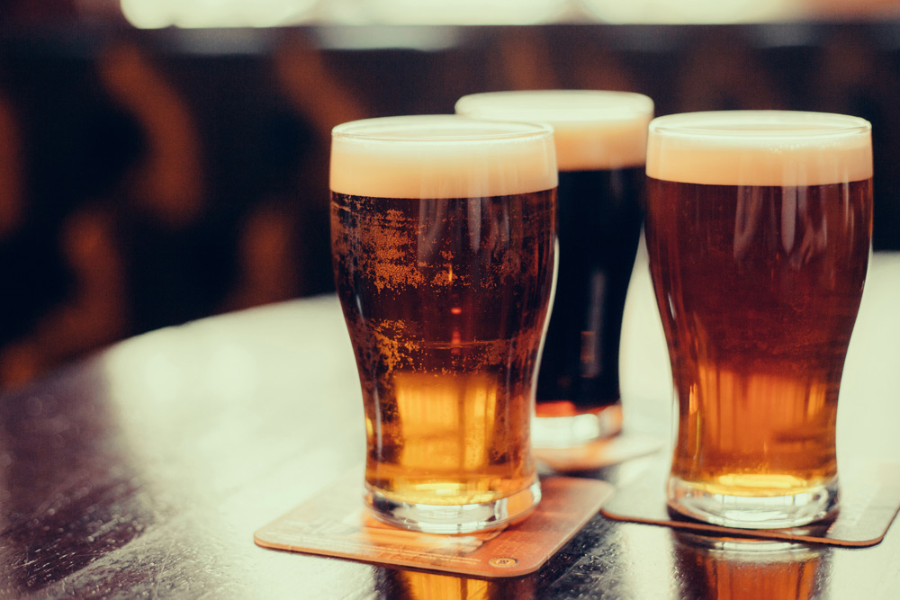 Pint glasses of beer on a table, as one of the best bachelor party ideas in Montreal