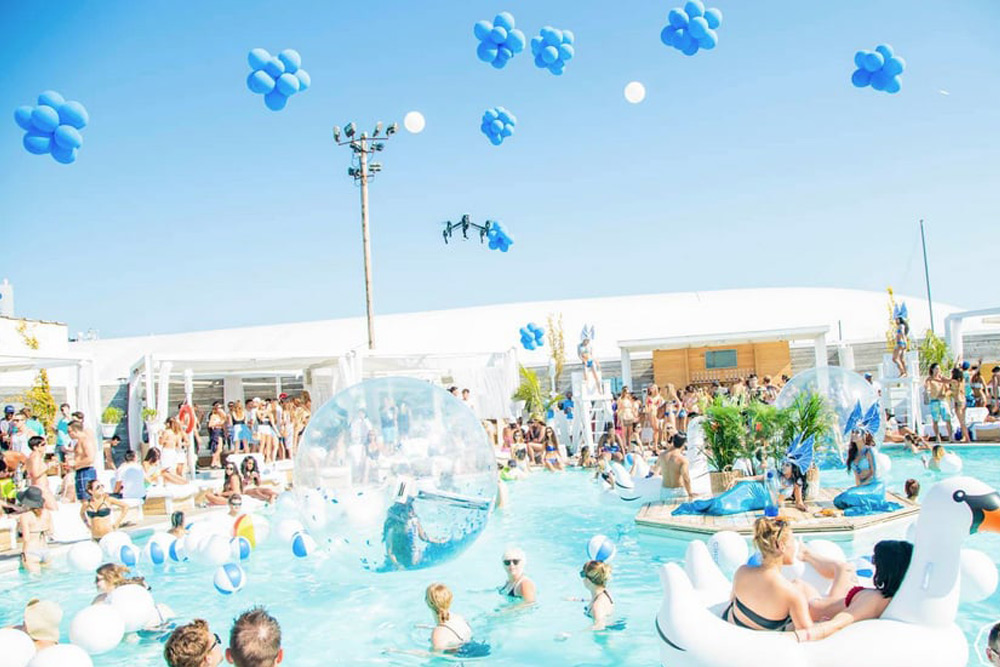 Group of people swim during a pool party, a top activity for a bachelor party in Toronto