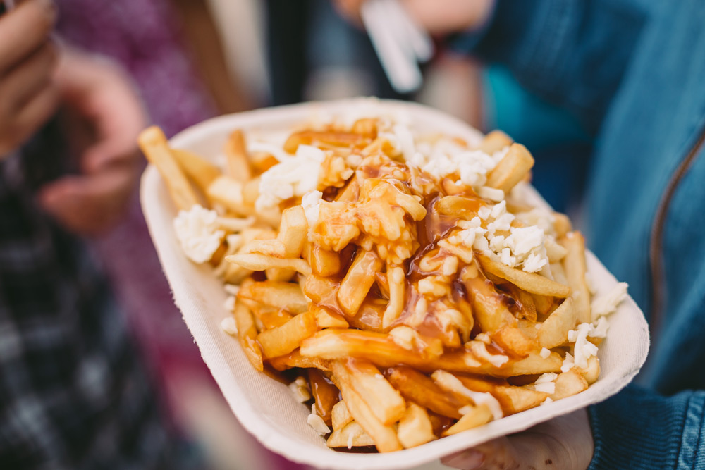 Plate of piping hot poutine on a food tour, a top bachelor party idea in Montreal