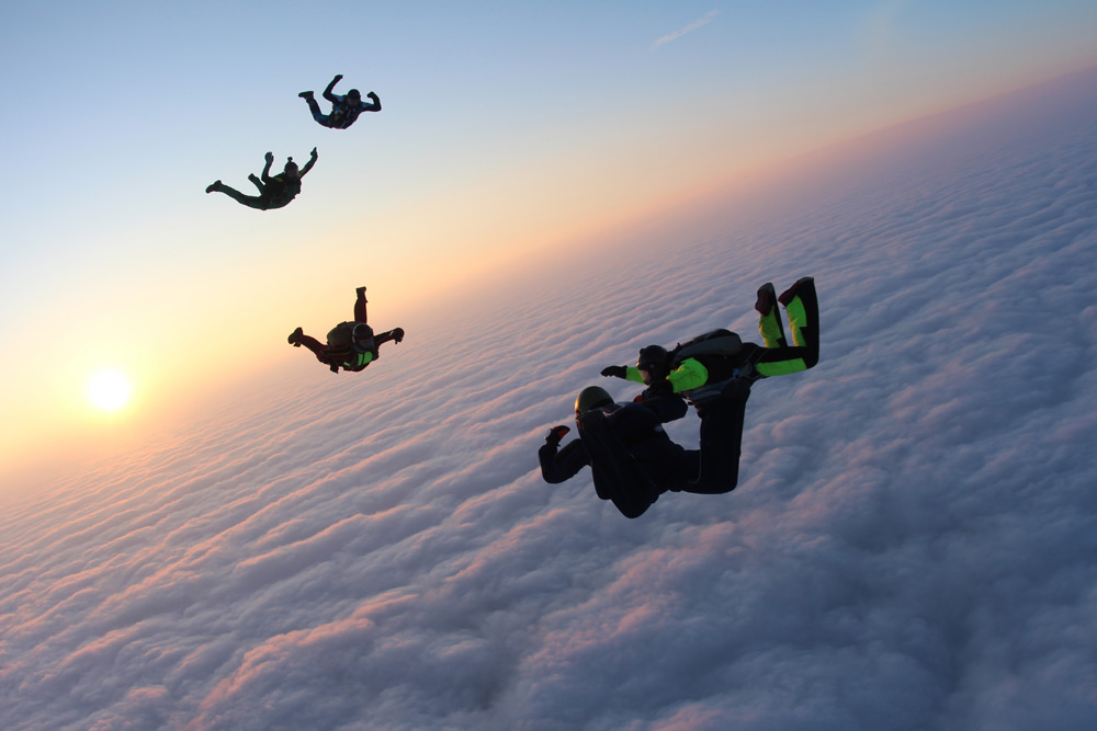 Group of people skydive through the clouds, one of the top activities for a bachelor party in Toronto