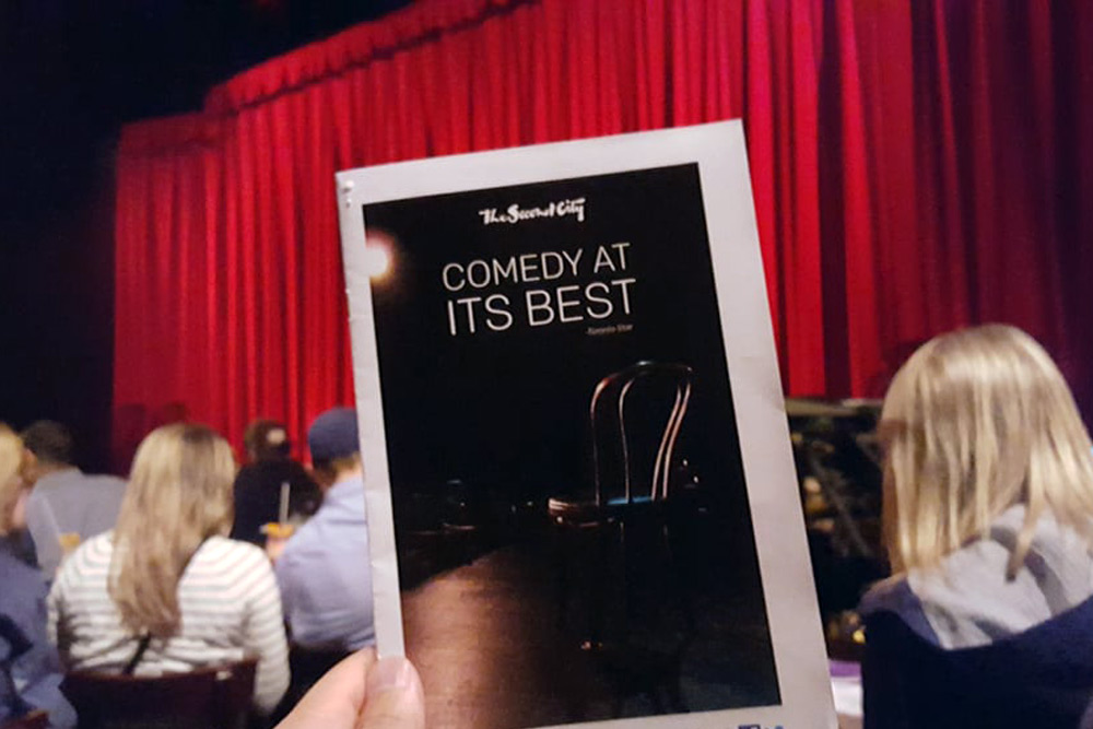 Audience member holds up a program at The Second City, one of the best places to go on a bachelor party.