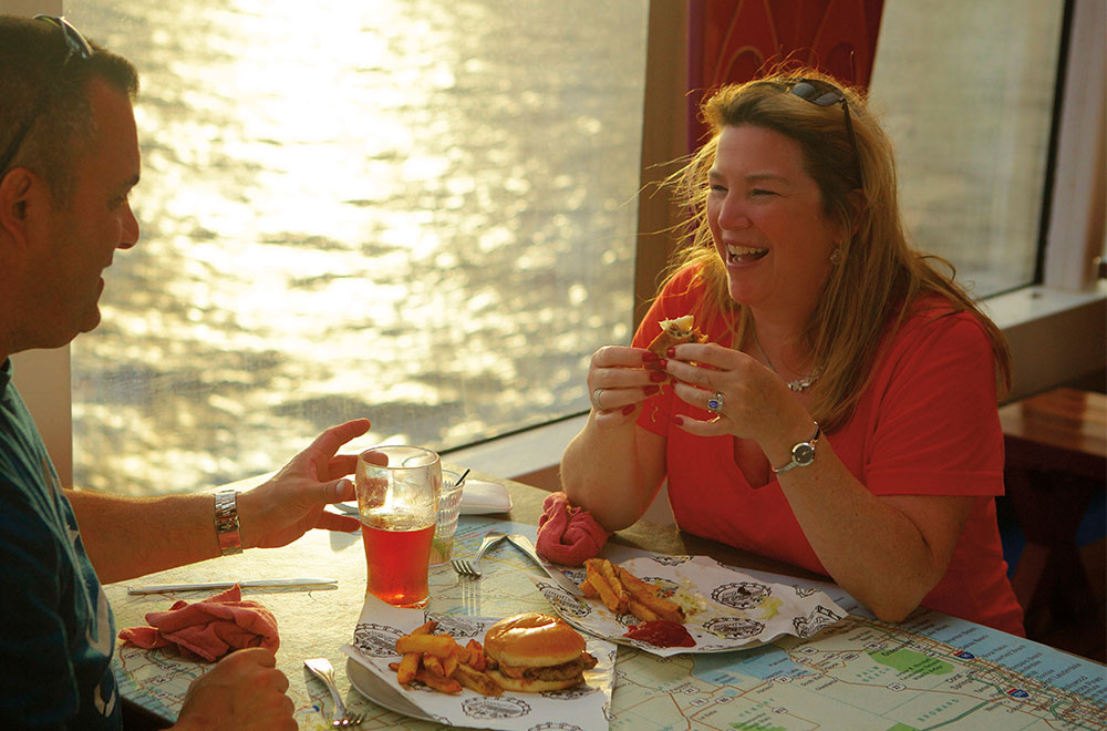 A cruise couple enjoying their meal at Guy's Burger Joint