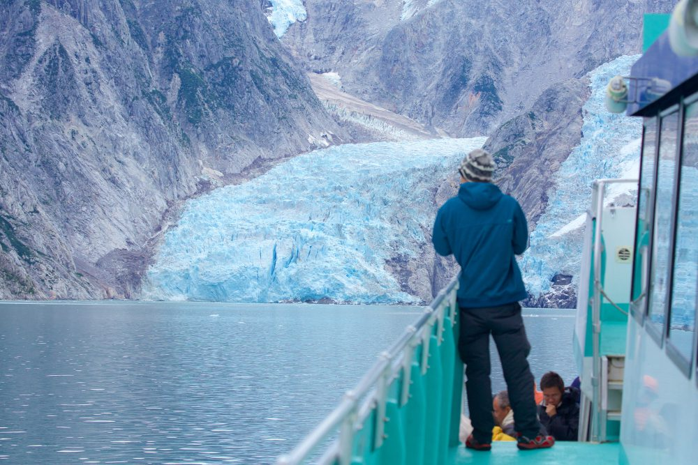 Passenger from a boat look at a glacier