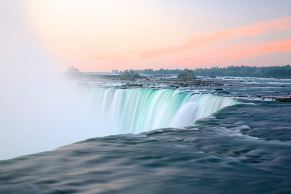 Sunrise image of Niagara Falls with a pink and blue sky