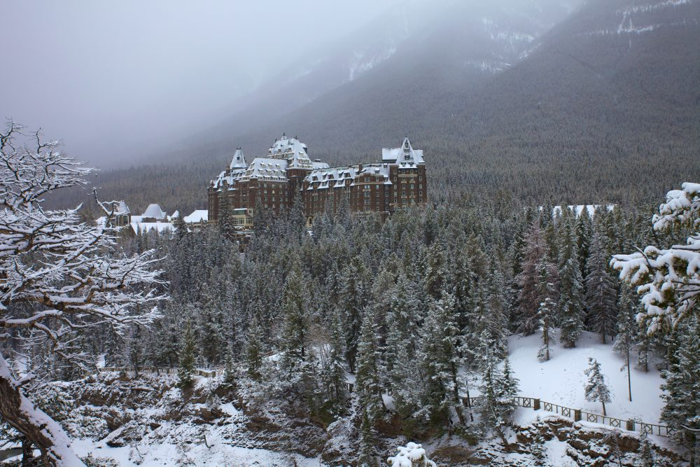 The Fairmont Banff Springs hotel sits in a pine-filled Rocky Mountain valley dusted with snow