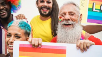 People having fun at Pride parade with LGBT banner outdoors.
