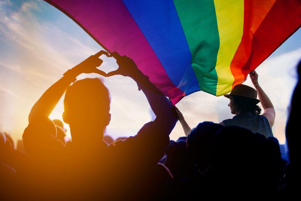 Pride community at a parade with hands raised and the LGBT flag