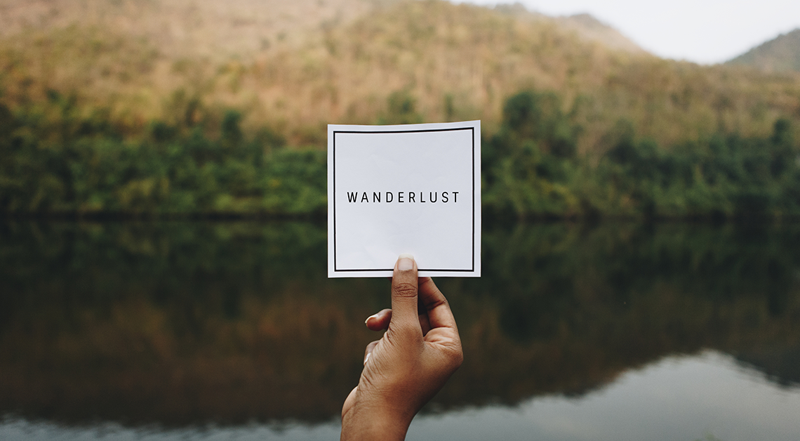 Hand holding up a sign that says wanderlust